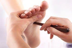 Reflexologist performing a reflexology technique on a client's foot
