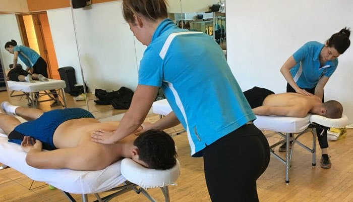 Women giving massages in a gym