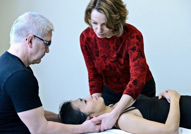 Massage teacher showing a student how to perform neck massage techniques