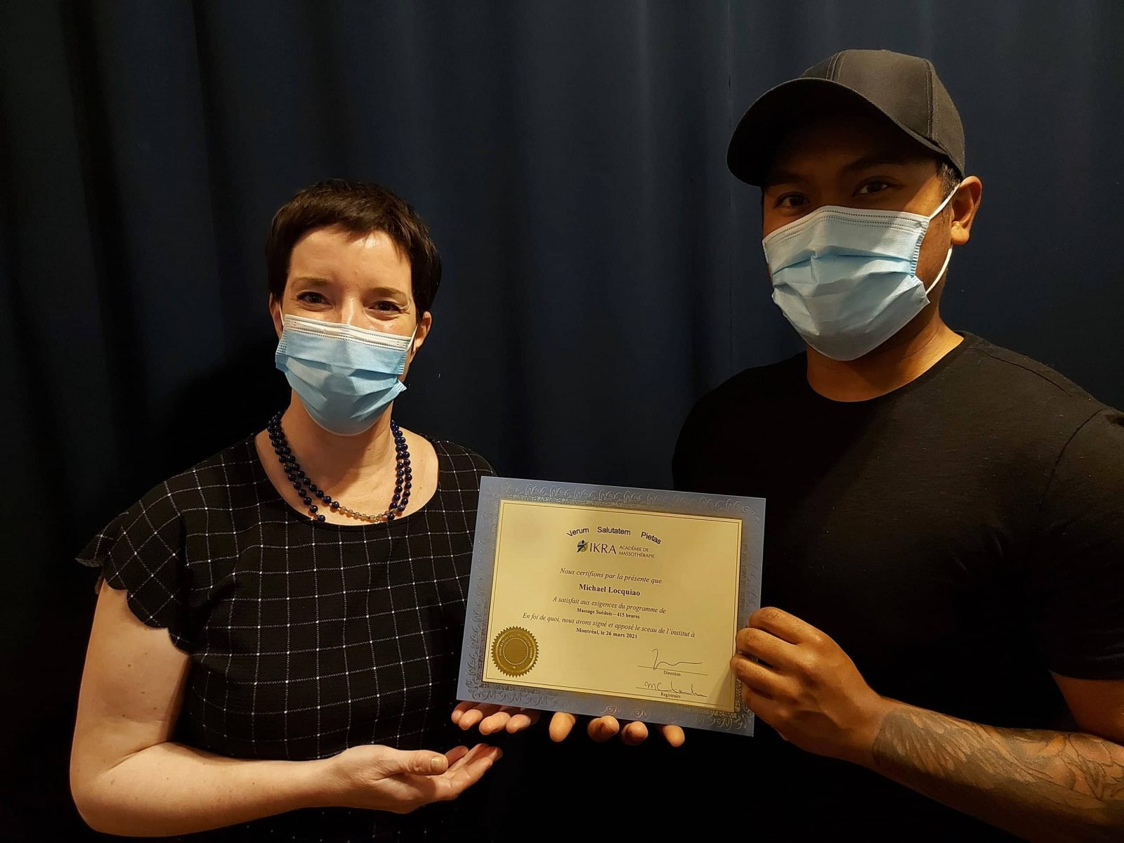 Michael Locquiao receives his diploma from IKRA Academy of Massage Therapy