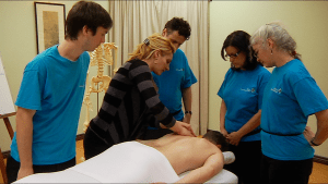 Students learning from a massage therapy teacher