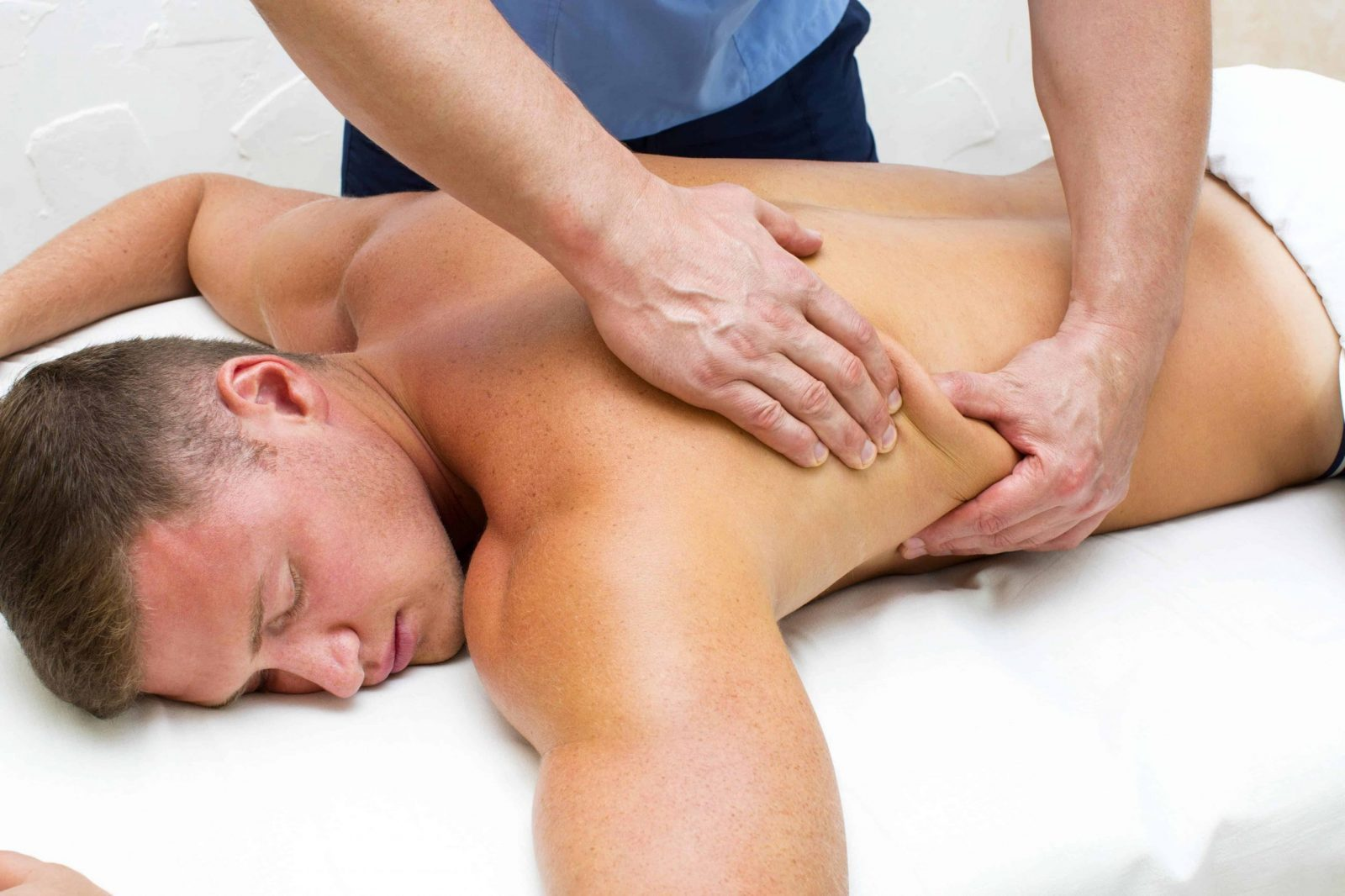 A massage therapist using an advanced technique on a client.